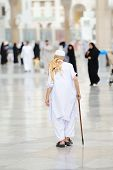 Aged Muslim pilgrim walking in front of Mecca mosque