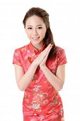 Smiling Chinese woman dress traditional cheongsam at New Year, studio shot isolated on white backgro