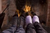 Couples'S Feet Warming At A Fireplace