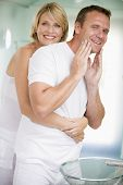 Couples In Bathroom Embracing And Smiling