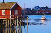 stock photo of hamlet  - Typical red rorbu hut with sod roof lit by midnight sun in town of Reine on Lofoten islands in Norway - JPG
