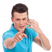 waist-up picture of an attractive young casual man pointing and looking angrily at the camera while
