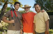 Portrait of happy men standing together with pruner at lawn