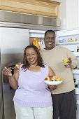 Portrait of an obese African American couple standing by an open fridge at home