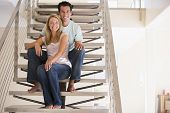 Couples Sitting On Staircase Smiling