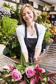 image of flower shop  - Woman florist wrapping bunch of flowers - JPG