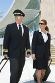 image of cabin crew  - Happy airplane cabin crew walking together at the airport with bags - JPG