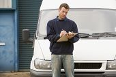 Deliveryperson Standing With Van Writing In Clipboard