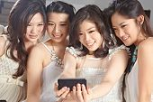 Four young women taking picture using cell phone camera