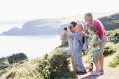 Families On Cliffside Path Using Binoculars And Smiling