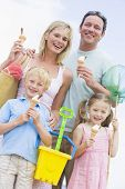 Families At Beach With Ice Cream Cones Smiling