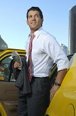 Handsome businessman getting out of taxi