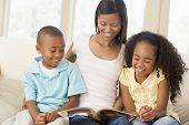 Woman And Two Children Sitting In Living Room Reading Book And Smiling