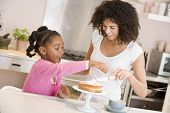 Woman And Young Girl In Kitchen Icing A Cake Smiling