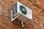 Air Conditioning Heat Pump Mounted On Old Brick Wall