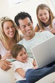 Families In Living Room With Laptop Smiling