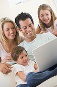 Familien im Wohnzimmer mit Laptop lächelnd