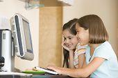 zwei junge Mädchen in Küche mit Computer lächelnd