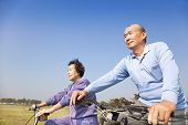 Happy Elderly Seniors Couple Biking