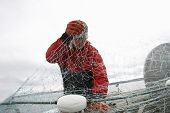 Fisherman detangling fishing net while standing in boat
