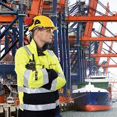 Docker, wearing a hard hat, gloves, safety glasses and a chemical resistant coat, sternly overlooking  an industrial harbor with large cranes, unloading containers from a freight ship
