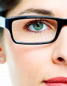 Woman's green eye in glasses close up