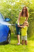 stock photo of pressure point  - Mother and three years old son washing car with high pressure washer with boy pointing water nozzle - JPG