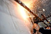 stock photo of pipe-welding  - Professional welder cutting and grinding metal pipes - JPG