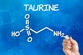 Hand with pen drawing the chemical formula of taurine