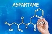 Hand with pen drawing the chemical formula of aspartame