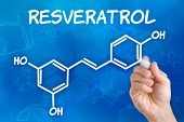 Hand with pen drawing the chemical formula of resveratrol