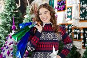 Happy young woman looking away while carrying shopping bags in Christmas store