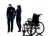 image of wheelchair  - one  man with woman  walking away from  wheelchair  in silhouette studio  on white background - JPG