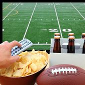 Closeup of a man's hand holding a TV remote with a bowl of chips and a six pack of beer with a footb