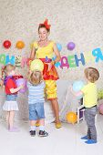 Three kids and facilitator play with balloons at funny children party. Inscription Happy Birthday on