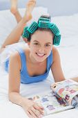 Girl in hair rollers lying in bed and smiling in camera reading magazine