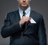 foto of tied hair  - Part of body of man who takes out white card from the pocket of business suit - JPG