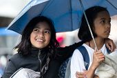 BANAUE, PHILIPPINES, DECEMBER 03:Two Filipina girls sheltering under an umbrella together as they walk down an urban street in village of Banaue, north Luzon, Philippines, on december 03, 2013