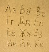 Russian alphabet (first part of three) written on a sand beach.