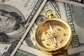 Gold compass on pile of US money