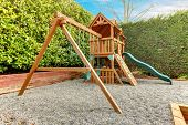 stock photo of chute  - Backyard playground with swings climbing wood panel chute - JPG