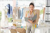 stock photo of self-employment  - Portrait of a beautiful female fashion designer with folder in the studio - JPG