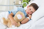 Portrait of sick little boy with teddy bear in hospital bed