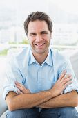 Cheerful man sitting on the couch smiling at camera at home in the living room