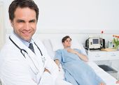Portrait of confident male doctor in hospital with patient lying on bed in background