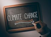 Hand writing the word climate change on black chalkboard