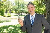 Portrait of happy businessman holding smart phone in park