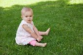 Full length of a cute baby sitting on grass at the park