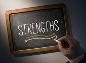 Hand writing the word strengths on black chalkboard