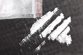 stock photo of crystal meth  - Cocaine powder in lines and packet on mirror closeup - JPG